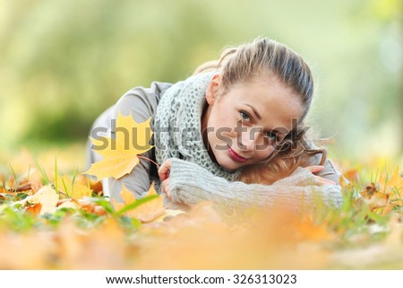 Young woman laying down on the ground in autumn park - stock photo