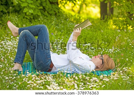 Young woman laying in the grass and reading a book  - stock photo