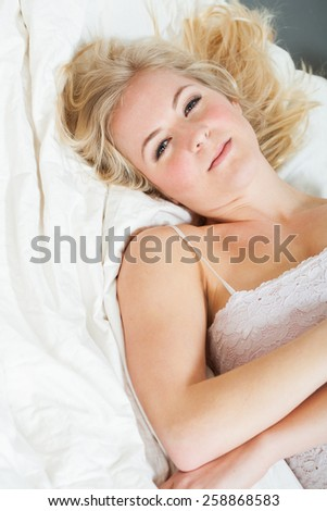 Young woman laying on a white comforter - stock photo