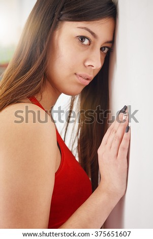Young woman leaning against the stone wall, looking at the camera. - stock photo