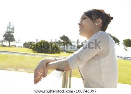 Young woman leaning on a metallic banister in a park, smiling. - stock photo