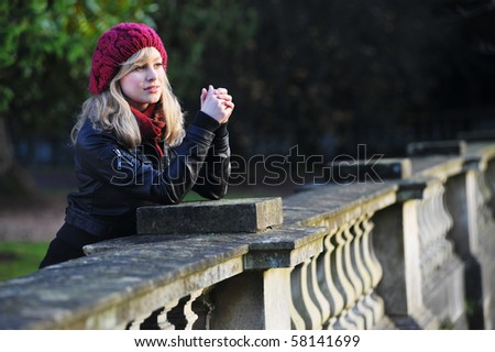 Young Woman Leaning On A Wall In Thought - stock photo