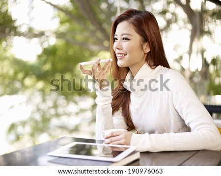 young woman leaving voice message using mobile phone. - stock photo