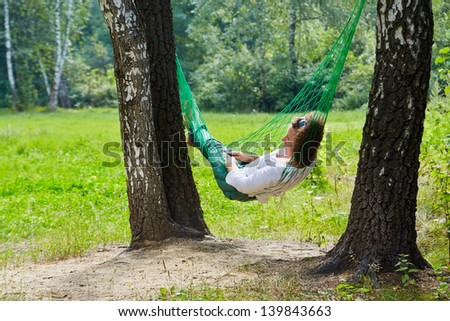 Young woman lies in hammock suspended between two thick birches - stock photo
