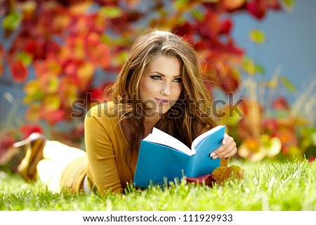 Young  woman lies on green grass and reads book against autumn  park. - stock photo