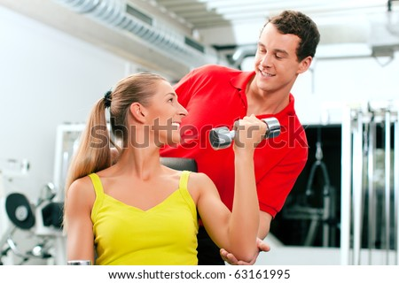 Young woman lifting a dumbbell in the gym assisted by her personal trainer (focus on woman) - stock photo