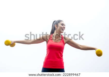 young woman lifting dumbbells outdoor - stock photo