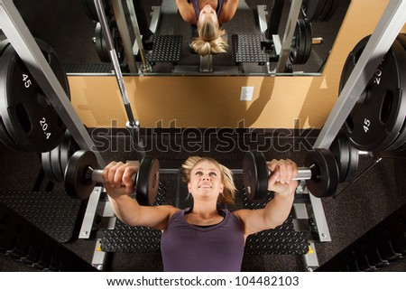 Young Woman Lifting Weights in Fitness Center - stock photo