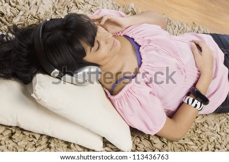 Young woman listening music in a living room - stock photo