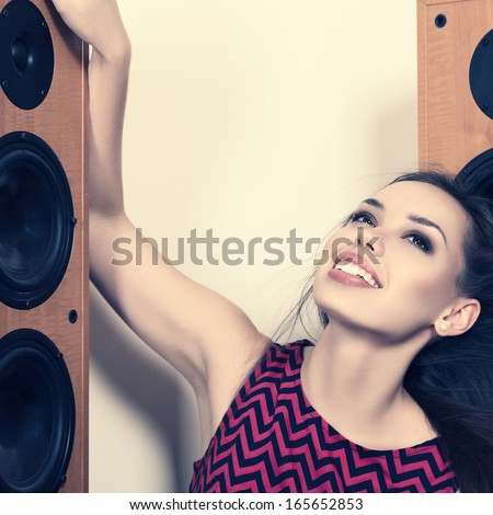 Young woman listening music in front of big speakers - stock photo
