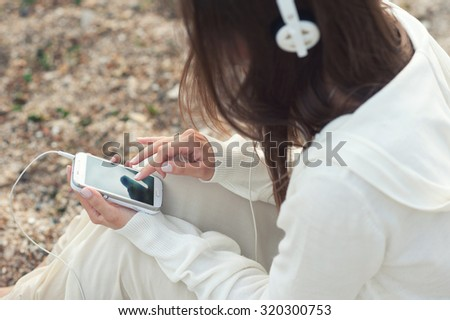 Young woman listening music with phone against sea sand backdrop, back view. - stock photo