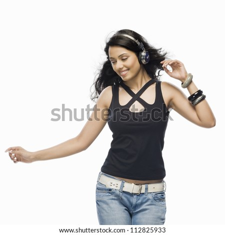 Young woman listening to music and dancing - stock photo