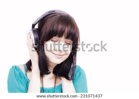 Young woman listening to music on earphones - stock photo