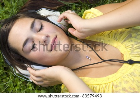Young woman listening to music outdoors - stock photo