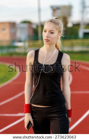 young woman listening to music while doing sport - stock photo