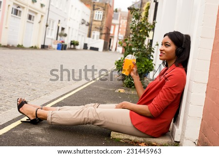 young woman listening to music with a fresh drink. - stock photo