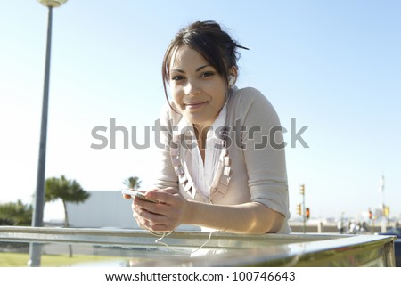 Young woman listening to music with headphones in the city, smiling and looking at camera. - stock photo