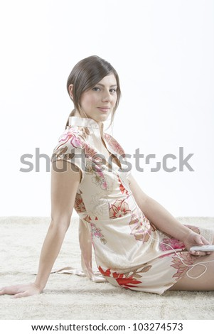 Young woman listening to music with her mp4 player while sitting on carpet. - stock photo