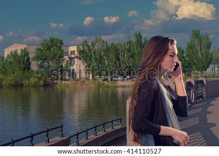 Young woman listening to the conversation using her mobile phone with serious expression on her face, she standing outdoors on granite embankment against river backdrop toned image a lot of copyspace. - stock photo