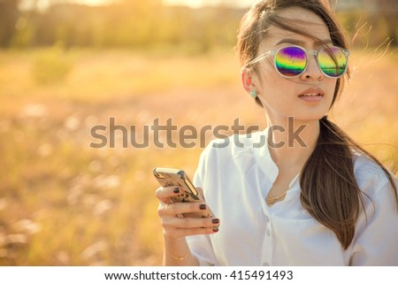 young woman lonely on meadow use mobile phone sunset time - stock photo