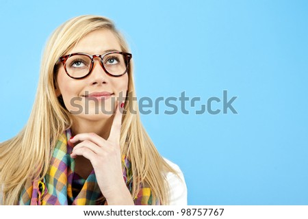 young woman look up on blue background - stock photo