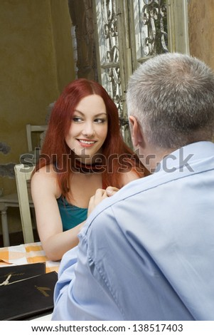 Young woman looking and flirting with another - Glance over his shoulder - Restaurant scene - Selective focus - stock photo