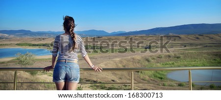Young woman looking at a beautiful view of the lake and mountains - stock photo