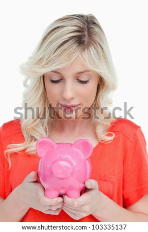 Young woman looking at a piggy bank held by her hands against a white background - stock photo