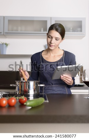 Young woman looking at a recipe on her tablet as she stands in the kitchen in front of a saucepan o the stove with fresh ingredients - stock photo