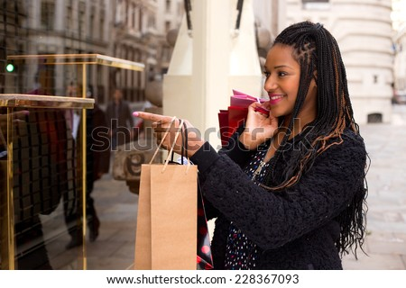young woman looking at a shop window display. - stock photo