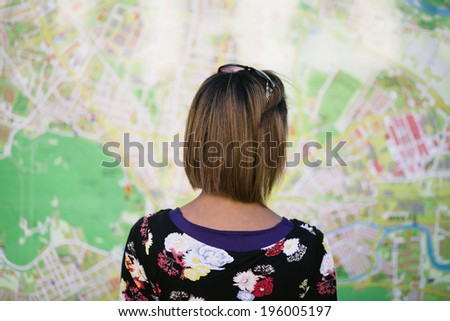 Young woman looking at big tourist city map - stock photo