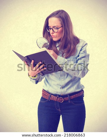 young woman looking at book by magnifying glass - stock photo