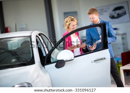 Young woman looking at brochure with salesman in car showroom - stock photo