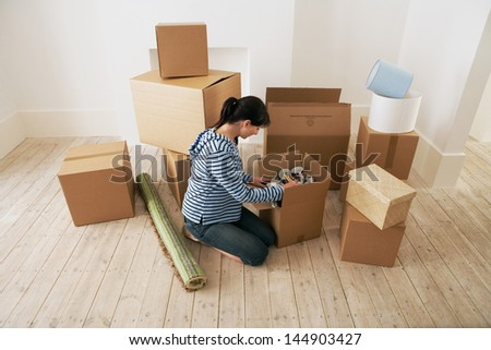 Young woman looking at contents of moving boxes in new home - stock photo