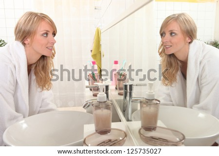 Young woman looking at her reflection in a bathroom mirror - stock photo