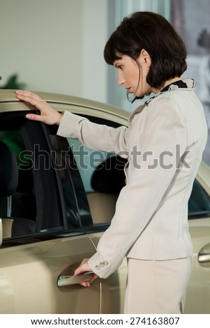 Young woman looking at new car - stock photo