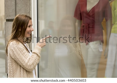 Young woman looking at shop window, showing on clothes with her finger. - stock photo