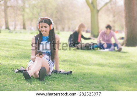Young woman looking at smart phone and listening music at park in London. She is lying on the grass, wearing colourful headphones on a London spring sunny day. - stock photo