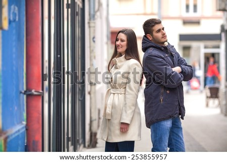 Young woman looking at store window and bored young man standing behind her back with his arms crossed waiting for her. - stock photo