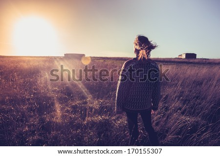Young woman looking at sunset in field with her hair blowing - stock photo
