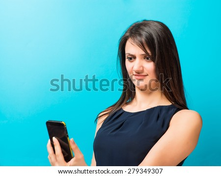 young woman looking at the phone, angry - stock photo