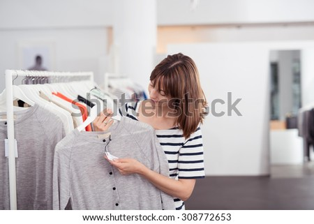 Young Woman Looking at the Price Tag of a New Casual Gray Shirt on a Hanger Inside a Department Store. - stock photo