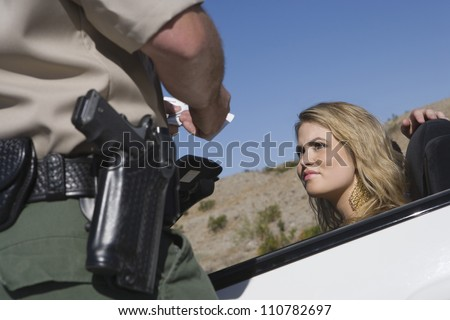 Young woman looking at traffic officer checking her license - stock photo