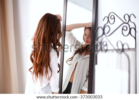 Young woman looking herself reflection in mirror at home - stock photo
