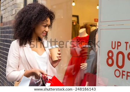 young woman looking in a shop widow with a coffee and shopping bags. - stock photo