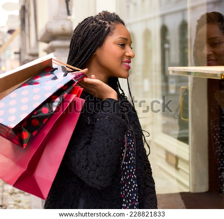 young woman looking in a shop window. - stock photo