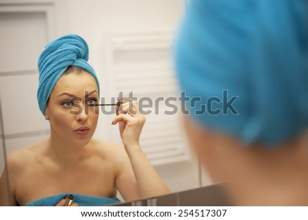 Young woman looking in the mirror and putting make-up on - stock photo
