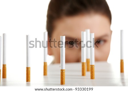 Young woman looking on cigarettes standing on white table. - stock photo
