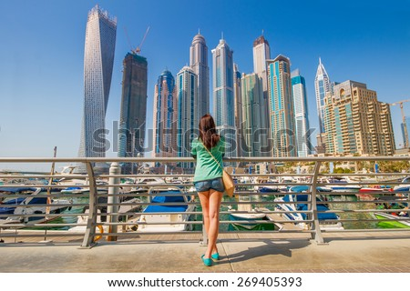 Young woman looking on skyscrapers in Dubai Marina - stock photo