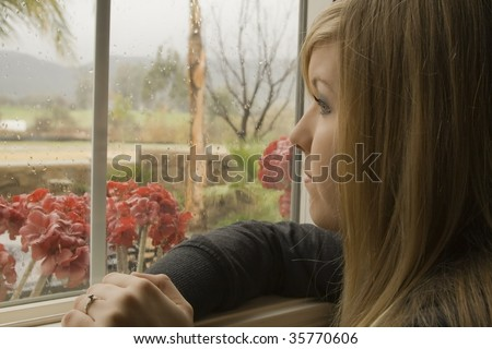 Young woman looking out a window on a rainy day. - stock photo